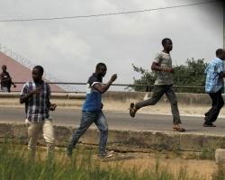 People run as they leave the port of Abidjan after hearing gunfire in Abidjan